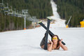 Cheerful naked female skier is lying on snowy slope near ski lift at resort Royalty Free Stock Photo