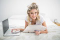 Cheerful natural blonde shopping online using laptop lying on cosy bed Stock Images