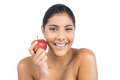 Cheerful nude brunette holding red apple on white background Stock Images