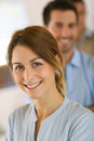 Cheerful office worker young girl standing in front of business team Royalty Free Stock Image