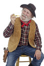 Cheerful old cowboy sits with holding cob pipe. Royalty Free Stock Photo