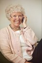 Cheerful old woman on phone smiling while calling her cell Stock Photos