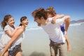 Cheerful parents piggybacking their children at beach Royalty Free Stock Photo