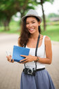 Cheerful pastime vertical portrait of a girl with a camera and a book enjoying her summer Stock Photography