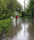 Cheerful playful toddler boy in a red raincoat, yellow rubber boots and a helmet rides a bicycle through a huge puddle Royalty Free Stock Photo