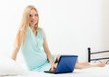 Cheerful pregnancy woman awaking with laptop on white sheet in her bed at home Stock Photos
