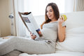 Cheerful pregnant woman eating apple and reading magazine on bed Royalty Free Stock Photo