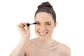 Cheerful pretty model applying mascara while posing on white background Stock Photography