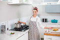 Cheerful pretty woman with apron cooking in bright kitchen Royalty Free Stock Photos