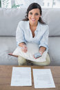 Cheerful pretty woman doing her accounts in living room Stock Image