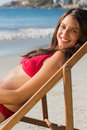 Cheerful pretty woman relaxing on her deck chair the beach Royalty Free Stock Images