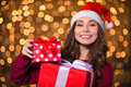 Cheerful pretty young woman in santa claus hat holding presents Royalty Free Stock Photo