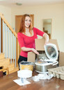 Cheerful red haired woman unpacking new crock pot on the table a at home Royalty Free Stock Images