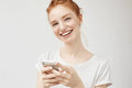 Cheerful redhead girl smiling holding phone.