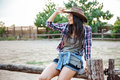 Cheerful relaxed young woman cowgirl sitting on fence and smiling Royalty Free Stock Photo