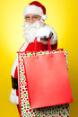 Cheerful Santa holding vibrant colored  bags Royalty Free Stock Image