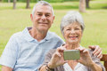 Cheerful senior couple photographing themselves at park Stock Photos