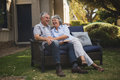 Cheerful senior couple sitting together on couch Royalty Free Stock Photo