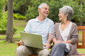 Cheerful senior couple using laptop at park Royalty Free Stock Photography