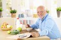 Cheerful senior man having breakfast healthy cereal for in kitchen smiling at camera Stock Photo