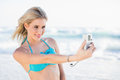 Cheerful sexy blonde in bikini taking a self picture on beautiful sunny beach Royalty Free Stock Photo