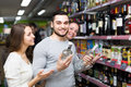 Cheerful shoppers choosing vodka Royalty Free Stock Photo