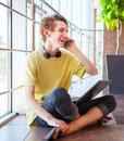 Cheerful smiling teenage boy talking by phone sitting on the floor Stock Photos