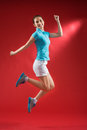 Cheerful sportswoman a jumping over a red background Stock Image