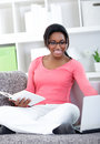 Cheerful student learning at home female on sofa in living room Royalty Free Stock Photos