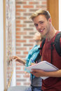 Cheerful student searching something on notice board Royalty Free Stock Photo