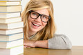 Cheerful student teenager look from behind books looking stack of glasses Royalty Free Stock Images