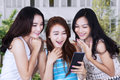 Cheerful students with cellphone at school group of three female laughing together when read a message on in front of building Royalty Free Stock Photography