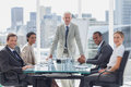 Cheerful team of business people in the meeting room with boss standing middle Royalty Free Stock Photo