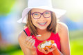 Cheerful teenage girl with dental braces glasses and ice cream. Portrait of a smiling pretty young girl in summer outfit with ice