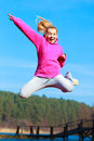 Cheerful teenage girl jumping showing outdoor full length of woman in pink tracksuit high pointing at something healthy active Stock Photography