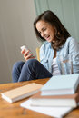 Cheerful teenage girl looking mobile phone home at read funny sms Stock Photography