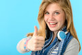 Cheerful teenage girl showing thumbs up isolated on blue background Stock Image