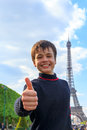 Cheerful teenager shows thumb up near Eiffel Tower Royalty Free Stock Photo