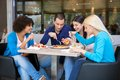 Cheerful teenagers having lunch in restaurant smiling and talking Royalty Free Stock Image
