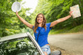 Cheerful travel woman on summer vacation leaning out of a car window she is holding map with arms raised Stock Photos