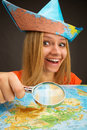Cheerful traveler girl discovering map with magnifier Royalty Free Stock Photo