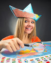 Cheerful traveler girl discovering map with magnifier Royalty Free Stock Image