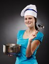 Cheerful woman cook holding a pot and a soup ladle studio shot of over gray background Stock Photography