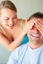 Cheerful woman covering his boyfriend's eyes Stock Images
