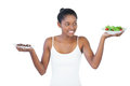 Cheerful woman deciding to eat healthily or not on white background Royalty Free Stock Photos