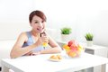 Cheerful woman drinking an orange juice sitting on her sofa at home asian beauty Stock Images