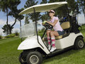 Cheerful woman driving golf cart female golfer in course Royalty Free Stock Photos