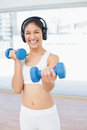 Cheerful woman exercising with dumbbells in fitness studio portrait of a fit bright Royalty Free Stock Photos