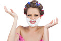 Cheerful woman with hands up and shaving foam on face white background Stock Image