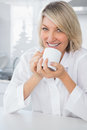 Cheerful woman having coffee in the morning sitting at counter kitchen Stock Photo